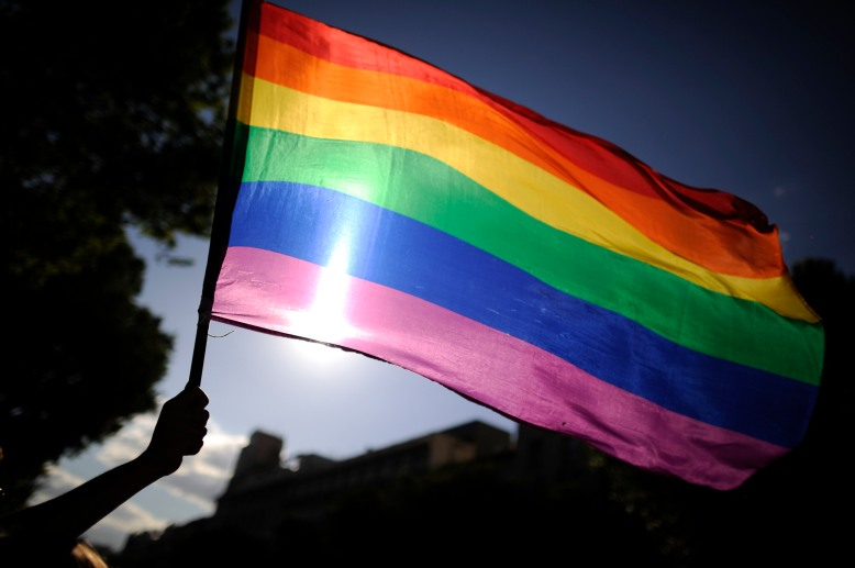 A participants holds a rainbow flag duri